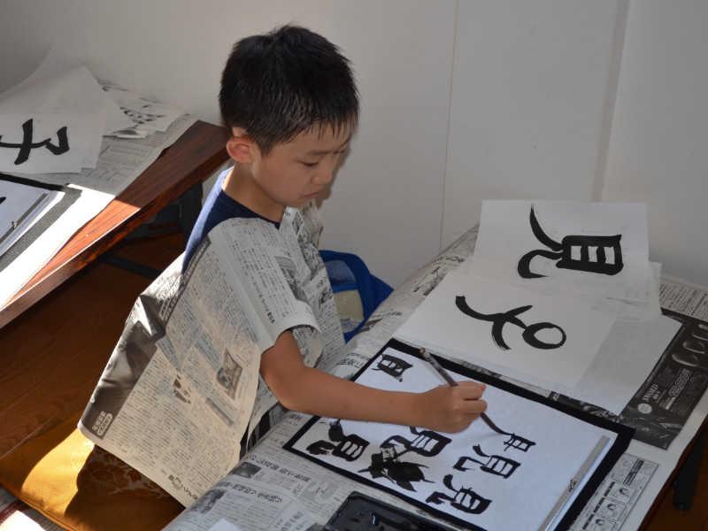 Elève qui apprend la calligraphie dans une école japonaise