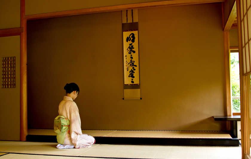 Méditation zen devant la calligraphie exposée dans un tokonoma